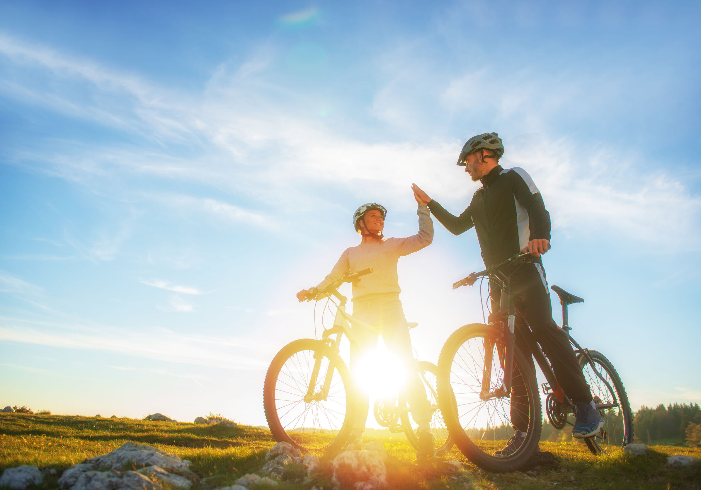 happy couple goes on a mountain road in the woods on bikes with helmets giving each other a high five.