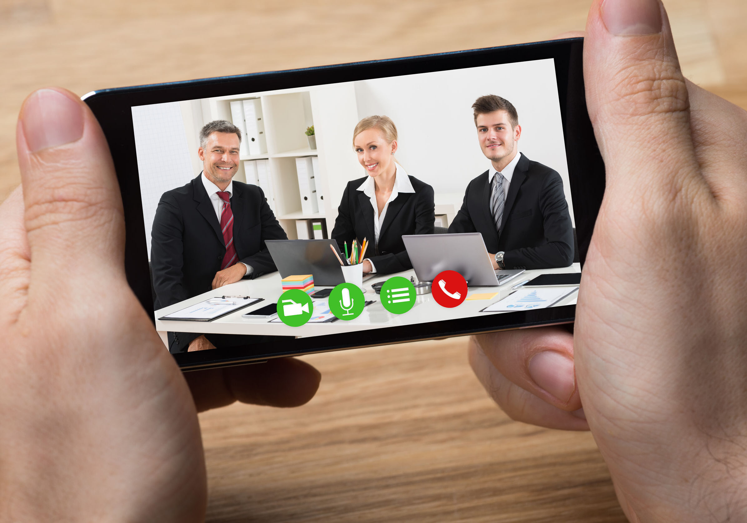 Cropped hands of businessman video conferencing with colleagues on smartphone at desk